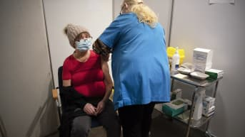 Sairaanhoitaja ja asiakas rokotushuoneessa Helsingin Messukeskuksessa.