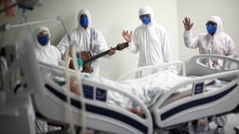 Terveysalan työntekijät laulavat ja rukoilevat koronaviruspotilaan sängyn vieressä.