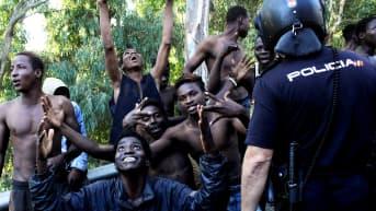 Siirtolaiset juhlivat espanjalaisen poliisin vieressä. Siirtolaiset onnistuivat pääsemään Marokon ja Espanjan välisen raja-aidan yli Espanjan puolelle.