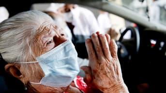 Vanhempi henkilö kiittää jumalaansa saatuaan koronarokotuksen Sao Paolossa.