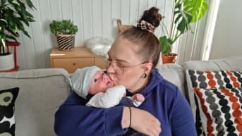 Emilia Merimaa suukottaa sylissään olevaa Nuutti-vauvaa.