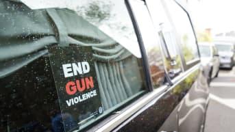 """""""Loppu aseväkivallalle""""-lappu ruumisauton ikkunassa."""
