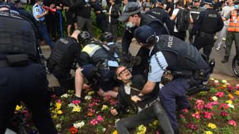 Maassa makaava mielenosoittaja ympärillään poliiseja.