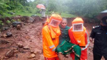 Pelastustyöntekijät kantavat naista.