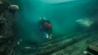 Sukeltaja ui vihreässä vedessä laivasta jääneiden lankkujen yllä.