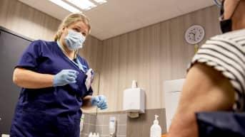 Seisova sairaanhoitaja Tiina Niemi juttelee tuolilla istuvalle potilaalle.