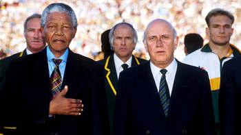 Presidentti Nelson Mandela kämmen rinnallaan laulaa kansallislaulu urheilutapahtumassa vierellään varapresidentti Frederik Willem de Klerk. Kuva peräisin 90-luvulta?