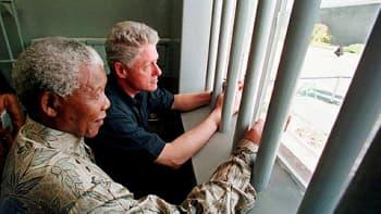 Etelä-Afrikan presidentti Nelson Mandela ja Yhdysvaltain presidentti Bill Clinton katsovat ulos sellin ikkunasta Robben Islandin saarella Etelä-Afrikassa.