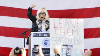 Lady Gaga puhuu lavalla mielenosoittajien edessä.