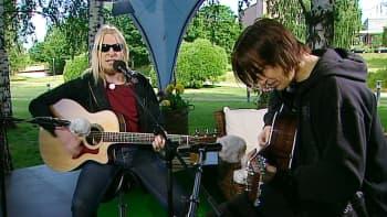 Kaksi miestä soittamassa kitaraa.
