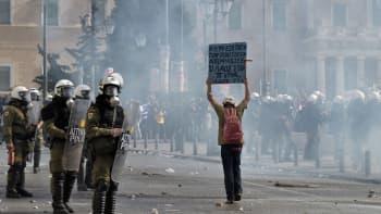 Mielenosoittaja kantaa kylttiä mellakkapoliisien edessä.