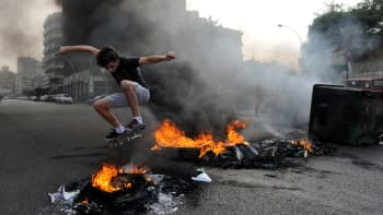 Libanonilaisnuorukainen skeittaa palavien renkaiden keskellä 20. lokakuuta.