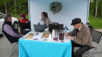 Kari Savolainen, Heli Kaski, Marika Paaso sekä ruskeatakkinen mies istuvat pöydän ääressä.