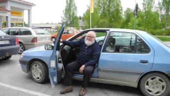 Mies istuu autossa Konneveden keskustassa