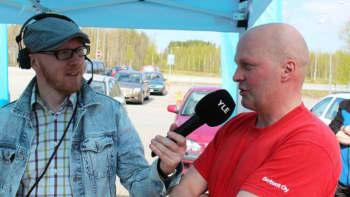 Mikko Maasola haastattelee punapuseroista miestä.