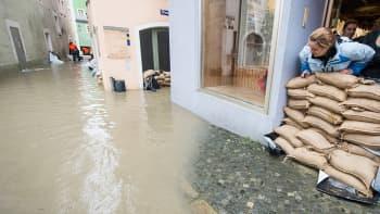 Kaupan työntekijä katselee nousevaa tulvavettä ovelle kasattujen hiekkasäkkien takaa.