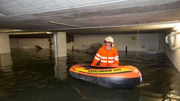 Palomies ja kumivene tulvivassa maanalaisessa autotallissa.