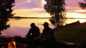 Miehiä iltanuotiolla auringon laskiessa.