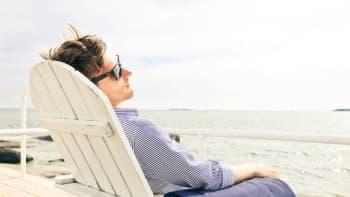 Mies istuu aurinkotuolissa.