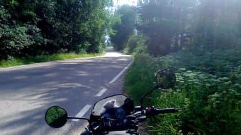 Moottoripyörä seisoo tien mutkassa.