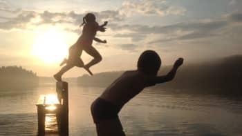 Lapsia hyppimässä laiturilta auringonlaskussa.