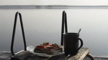 Voileipiä ja kahvikuppi jakkaralla laiturin nokassa.