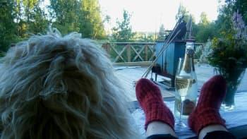Ihminen lepää jalat pöydällä viinipullo edessään.