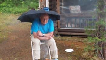 Mies paistaa makkaraa sateenvarjon alla.