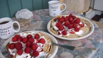 Lettuja ja mansikoita kahvipöydässä.