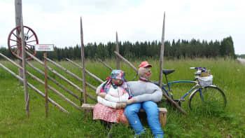 Kaksi linunpelätintä istuu penkillä pellon laidassa.