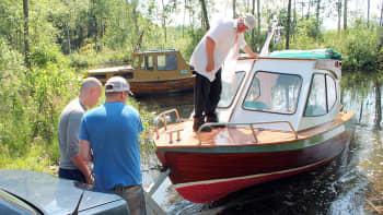Kolme miestä laskemassa venettä vesille.