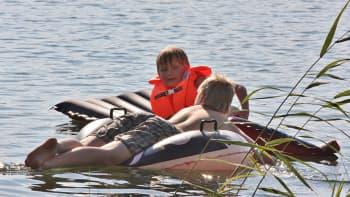 Lapset kelluvat uimapatjojen päällä
