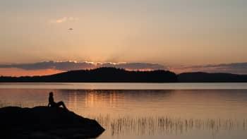 Hahmo ihastelee auringonlaskua rantakalliolla