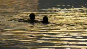 Pariskunta uimassa iltahämärässä