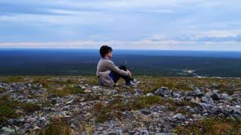 Nainen istuu tunturin laella ihailemassa maisemia
