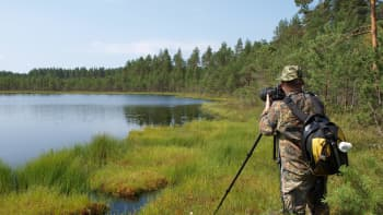 Luontokuvaaja kuvaamassa järven rannalla