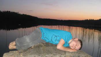 Poika makaa rantakivellä