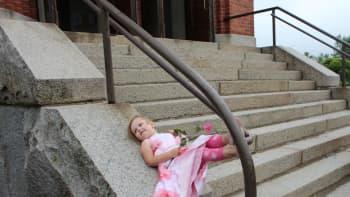 Tyttö makaa selällään kirkon portailla