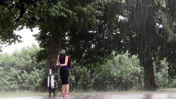 Pyöräilijä suojassa puun alla vesisaateessa