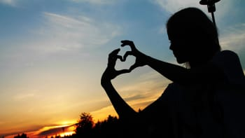 nainen tekee sormillaan sydänkuvion