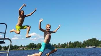 kaksi poikaa hyppäämässä veteen uimalaiturilta