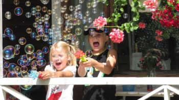 Poika ja tyttö leikkivät saippuakuplilla