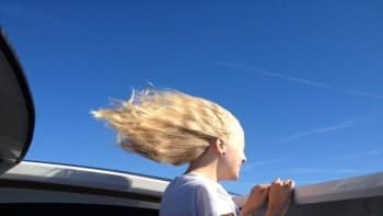 Veneen kyydissä olevan tytön hiukset hulmuavat tuulessa