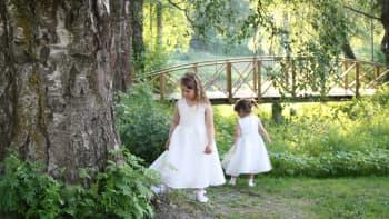 Kaksi tyttöä valkoisissa mekoissa tutkivat ympäristöä