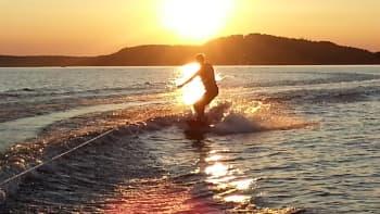 Poika harrastaa wakeboardausta auringonlaskussa