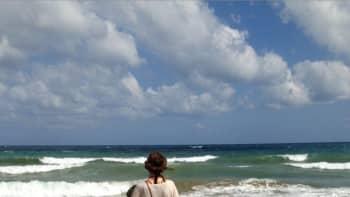 Tyttö merenrannalla katsomassa horisonttiin