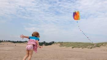 Tyttö lennättää leijaa hiekkarannalla