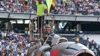 Usain Bolt vilkuttaa stadionyleisölle lentokoneen suihkumoottoria muistuttavan ajoneuvon päältä.