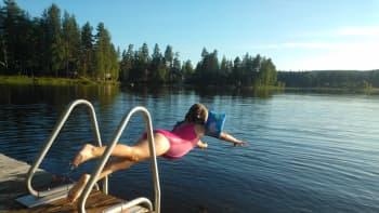 Tyttö hyppää laiturilta veteen