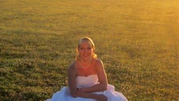 Morsian häämekossa kyykyssä sumuisen pellon laidalla auringon paistaessa takaa